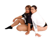 Two lovely young woman sitting on floor. Royalty Free Stock Images