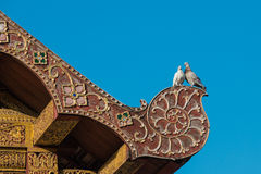 Two Lover Pigeon on the ancient Thai art style roof Stock Photo