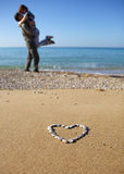 Two lovers on the beach. Heart on foreground and two lovers on background Royalty Free Stock Photo