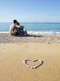 Two lovers on the beach. Heart on foreground and two lovers on background Royalty Free Stock Image