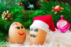 Two lovers celebrate Christmas . Unusual eggs with the muzzle. T. Wo eggs the love . The cartoon Christmas decorations Stock Photos