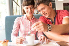 Two lovers chatting and having fun in the cafe Stock Images