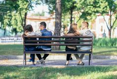 Two lovers couples sitting on different ends of one bench. Young happy men and women communicate with each other. Double date, youth, relationship, flirt royalty free stock photography