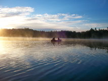 Two lovers drift in their canoe on a early morning Stock Images