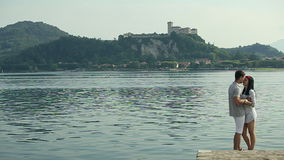 Two Lovers Embrace and Kiss at the Lake in Italy. August 2015 Arona city stock footage