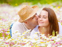 Two lovers on floral meadow. Two happy lovers laying down on white floral meadow, handsome guy kissing his cute girlfriend, relaxation outdoor, romance concept Stock Image