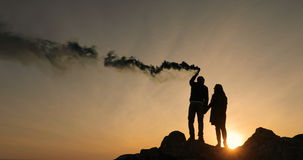 Two lovers hold a smoke bomb in their hands, on the background of a sunset, they sign the SOS. They want to survive stock video