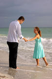 Two lovers holding hands and talking at the beach Stock Photos