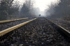 Two lovers holding hands walking on the train tracks. In winter Stock Images