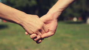 Two lovers joining hands. And walking away. Real time. Shallow depth of field stock video footage