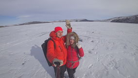 Two lovers on the lake ice. Two lovers travel along the snow-covered ice of the lake holding an action camera on the self-stick. They walk, spin and play stock video