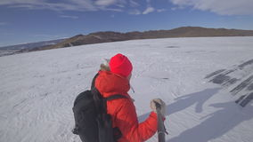 Two lovers on the lake ice. Two lovers travel along the snow-covered ice of the lake holding an action camera on the self-stick. They walk, spin and play stock video footage