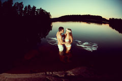 Two lovers in a lake at night. Girl and man at sunset in the lak Royalty Free Stock Image
