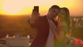 Two lovers a man and a woman laugh and take a photo selfie on the phone. Slow motion selfie summer together