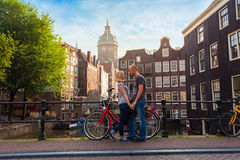 Two lovers person in Amsterdam on a background of multi-colored house in the Dutch style stand and hold hands. Meeting of loving couple in the morning on the Stock Images