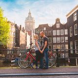 Two lovers person in Amsterdam on a background of multi-colored house in the Dutch style stand and hold hands. Meeting of loving couple in the morning on the Royalty Free Stock Photos