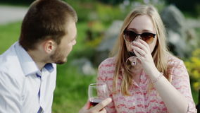 Two lovers on a picnic. Two lovers drink red wine on a picnic. Man gives a cherry to his girlfriend and they laugh stock video footage