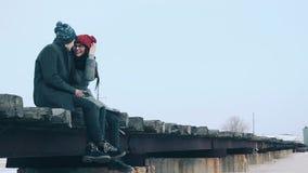 Two lovers romantic man sitting on the bridge, they hug and kiss. Two lovers romantic man in a coat and knit cap, sitting on the bridge stock video