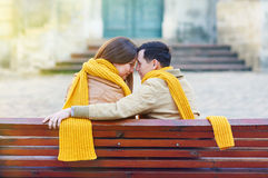 Two lovers sitting on bench in park and holding themselves by hands Stock Photos