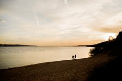 Two lovers stroll along the river at sunset. royalty free stock images