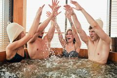 Group of caucasian diverse friends enjoying jacuzzi in hotel spa. Two loving couple enjoying hot wooden whirlpool with warm water in modern bathhouse of a luxury royalty free stock images