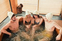 Group of caucasian diverse friends enjoying jacuzzi in hotel spa. Two loving couple enjoying hot wooden whirlpool with warm water in modern bathhouse of a luxury stock photo