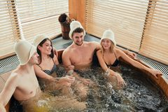Group of caucasian diverse friends enjoying jacuzzi in hotel spa. Two loving couple enjoying hot wooden whirlpool with warm water in modern bathhouse of a luxury royalty free stock photos