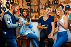 Two loving couples having fun at a bar and drink alcoholic bever Royalty Free Stock Image