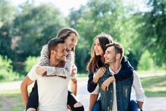 Two loving couples piggyback having fun outdoors Royalty Free Stock Photography