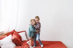 Two loving little kids standing on bed, hugging and smiling royalty free stock photo