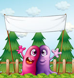 Two loving monsters under the empty banner Stock Image