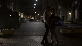 Two loving people kissing tenderly in night street, love in big city, dating. Stock footage stock footage