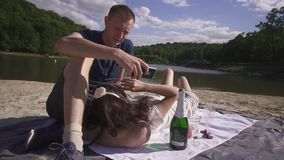 Two lovres on a picnick relaxing with wine and sweets on the beach on hot summer day untill man starts texting on the stock footage