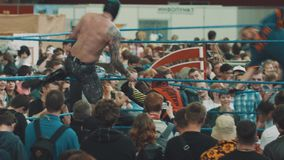 Two luchador wrestlers in masks fights on ring at crowded indoor festival. Grabbing and spinning moves stock video footage