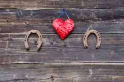 Two luck symbols rusty horsehoe and red cloth heart on wall Stock Image