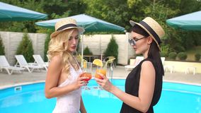 Two sexy girls clink cocktails around the pool. Two luxurious girls in black and white swimwear with slender tanned body standing near the pool with a drink in stock footage