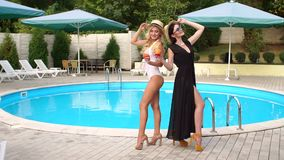 Two girls stand near the pool with a cocktail. Two luxurious girls with slender tanned body standing near the pool with a drink in hand, and posing for stock video