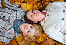 Two lying girls in leaves Royalty Free Stock Photos
