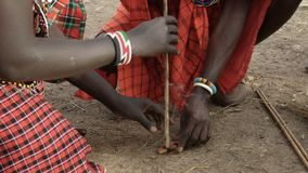 Two maasai men use a hand drill to start a fire at a manyatta in kenya. Two maasai men use a traditional hand drill to start a fire without matches at a manyatta stock footage