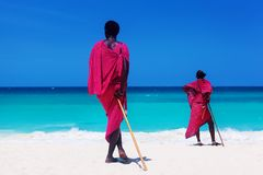 Two maasai warriors looking on ocean. Two maasai warriors looking at ocean on white sand beach at summer Stock Image