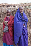Two Maasai women stand near their house look at my camera with wondering. Royalty Free Stock Photos