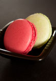 Two macarons. Rosa/purple and green macarons in a plate. Dark background with some dead space for custom text Royalty Free Stock Images
