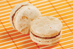Two macaroons on a bamboo table cloth Stock Image