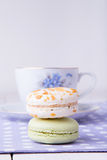 Two macaroons with cup of tea on polka dot towel Stock Photography