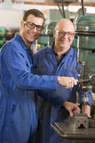 Two machinists working on machine Royalty Free Stock Images