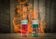 Two magic glass potions with Blue and red liquid on wooden table with yellow magic effect Stock Photo
