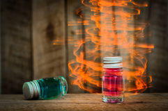 Two magic glass potions with Blue and red liquid on wooden table with yellow magic effect Stock Photography