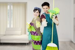 Two maids with thumbs up at home Royalty Free Stock Photography