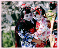Two Maiko wearing beautiful kimono. Nice lady with a girl in her arms - Two Maiko, chief and junior, the apprentice geisha, wearing beautiful kimono, аgainst Royalty Free Stock Photo