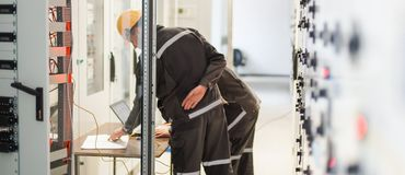 Two maintenance engineers inspect relay protection system with l. Aptop computer. Bay control unit. Medium voltage switchgear Stock Images